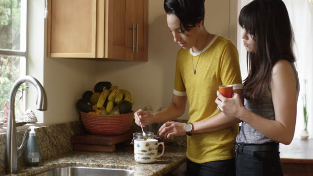 A young lesbian couple is having coffee and tea while preparing food in their kitchen