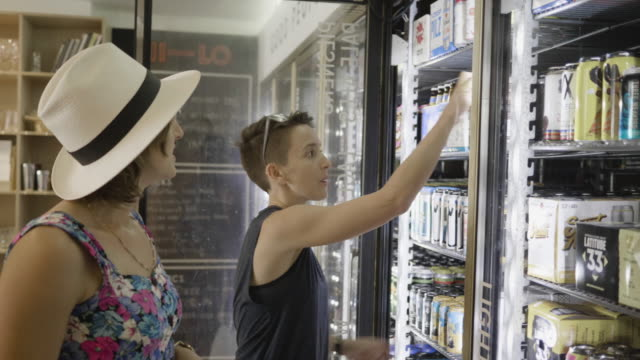 a young lesbian couple shop in the cooler section of a neighborhood market and wine shop, choosing different beers and cold drinks. - cool box stock videos & royalty-free footage