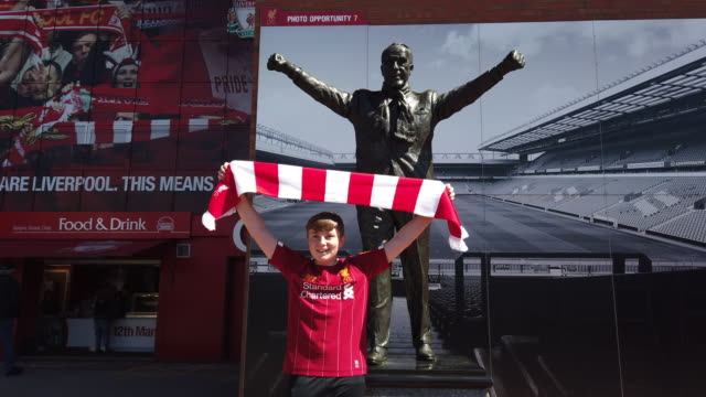 young liverpool fan posing for a photo in front of the state of bill shankly before liverpool's final premier league match of the season against... - neckwear stock videos and b-roll footage