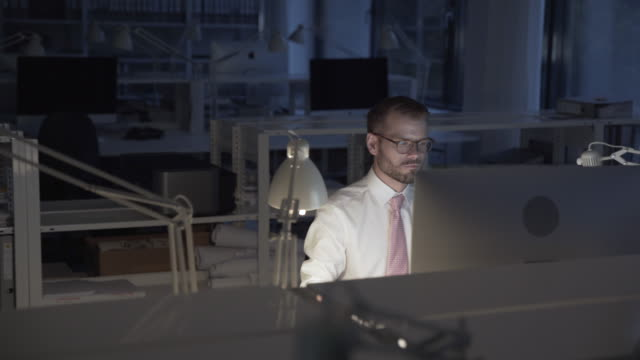 young lonely business man working late on computer in a creative, stylish office, berlin - 残業点の映像素材/bロール