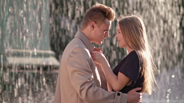 - young love couple meets in front of a fountain on a sunny day -