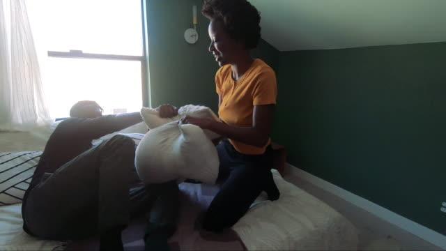 vídeos y material grabado en eventos de stock de joven encantadora negro pareja relajante en su casa jugando con almohadas - lucha con almohada