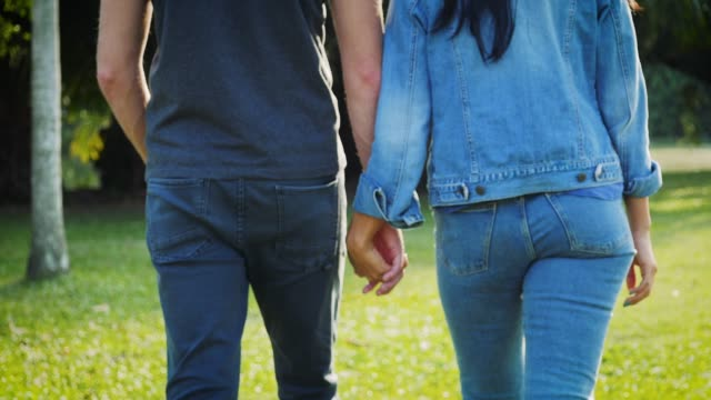 Young lover couple holding hands at green park outdoors, Romantic moments couple in love
