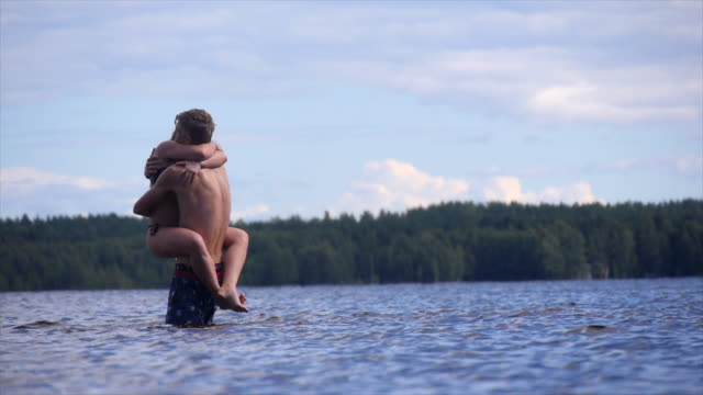 young lovers hugging in a shallow lake. - slow motion - goodsportvideo stock videos and b-roll footage