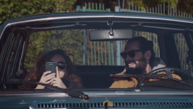 junges liebespaar sitzt in einem retro auto - girlfriend stock-videos und b-roll-filmmaterial