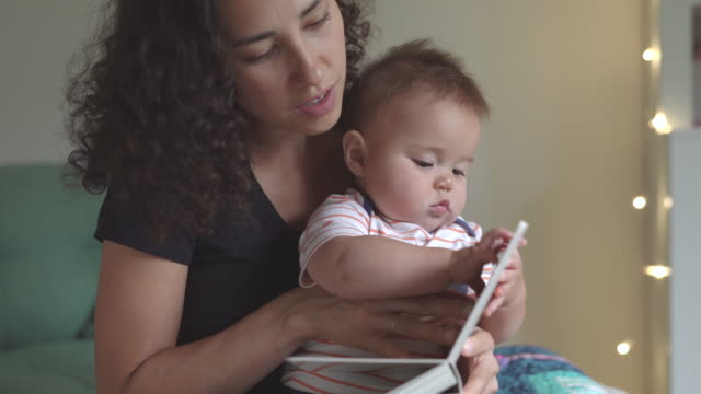 young loving mother reading bedtime storybook to adorable baby - pacific islanders stock videos & royalty-free footage