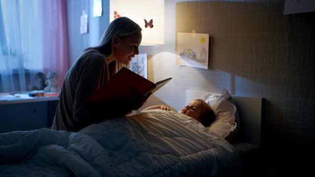 Young Loving Mother Reads Bedtime Stories to Her Little Beautiful Daughter who Goes to Sleep in Her Bed.