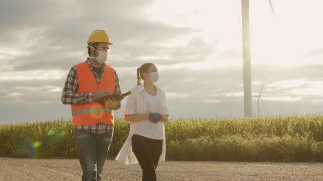 日没時に風力タービン農場で働く若いメンテナンスエンジニアと農学者チーム - 再生可能エネルギー点の映像素材/bロール