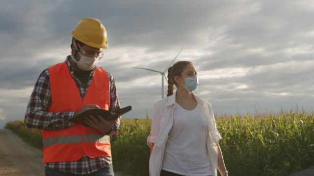 young maintenance engineer and agronomist team working in wind turbine farm at sunset - career stock videos & royalty-free footage