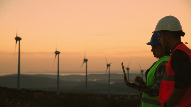 young maintenance engineer team working in wind turbine farm at sunset - landscaped stock videos & royalty-free footage