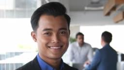 Young Malaysian businessman smiling towards camera