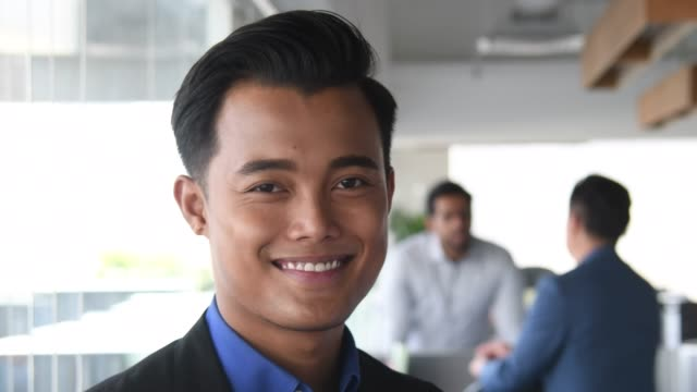 young malaysian businessman smiling towards camera - south east asian ethnicity stock videos and b-roll footage