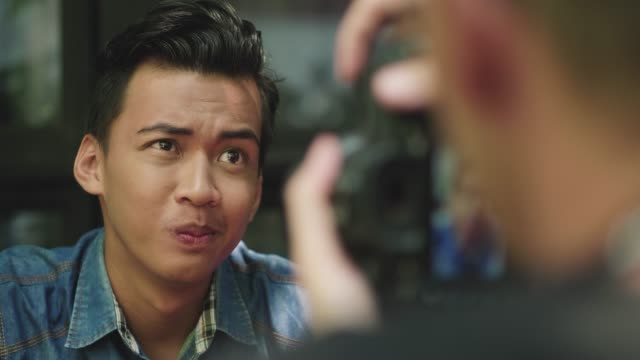 young malaysian man being photographed - photographer stock videos & royalty-free footage