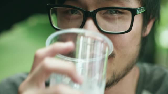 young malaysian man looking right at the camera - drinking glass stock videos & royalty-free footage