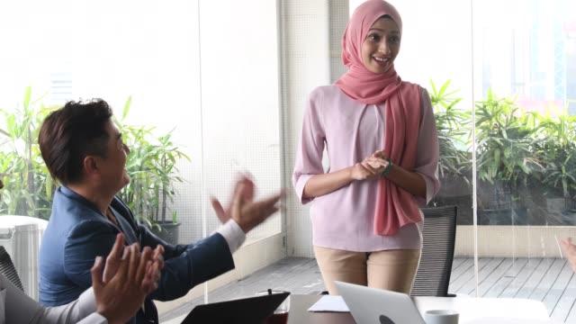 vidéos et rushes de jeune femme malaisienne en souriant et en appluaded - vêtement religieux