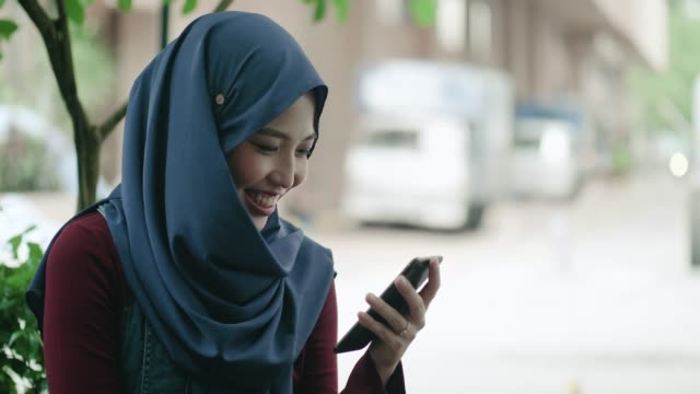 Young Malaysian Woman using a Mobile Phone