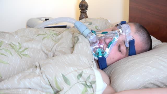 young male adult suffering sleep apnea - 無呼吸点の映像素材/bロール