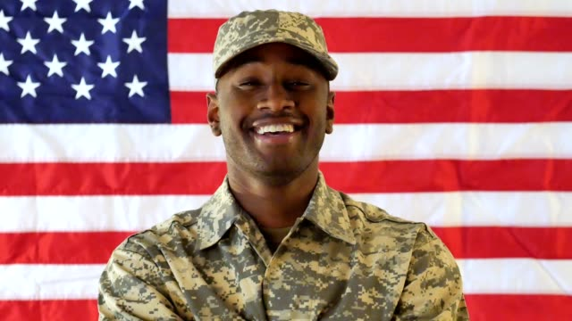 vídeos de stock e filmes b-roll de young male african american soldier smiles confidently while standing in front of the american flag - soldado exército