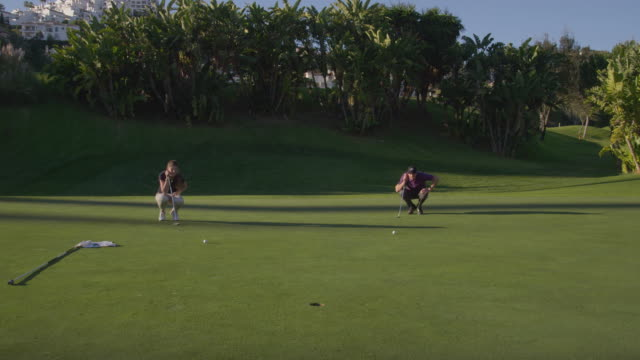 ts young male and female golfer entering green, looking at balls and hole; man takes shot and sinks ball, makes victory gesture;  camera tracks  (steadycam) red r3d 4k - ゴルフボール点の映像素材/bロール