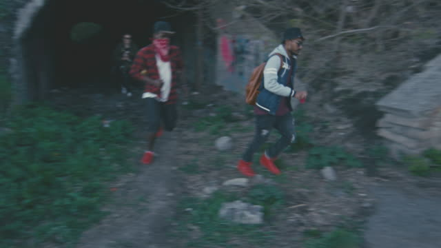 young male and female hooligans running - 公共物破壊点の映像素材/bロール