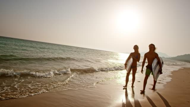 vídeos de stock, filmes e b-roll de surfista de masculino e feminina de slo mo jovens andando numa praia ao pôr do sol - calção