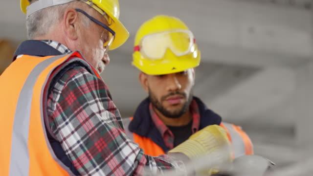 stockvideo's en b-roll-footage met jonge mannelijke leerling luisteren naar een senior mannelijke bouwvakker - werkhelm