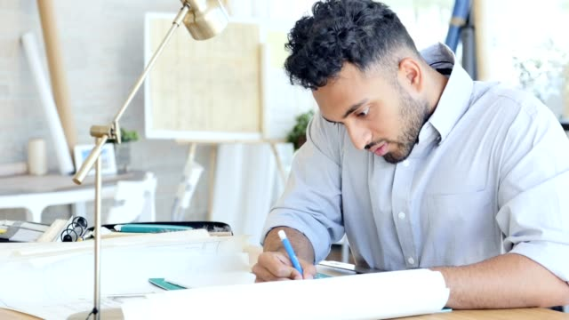 Young male architect concentrates while completing a blueprint