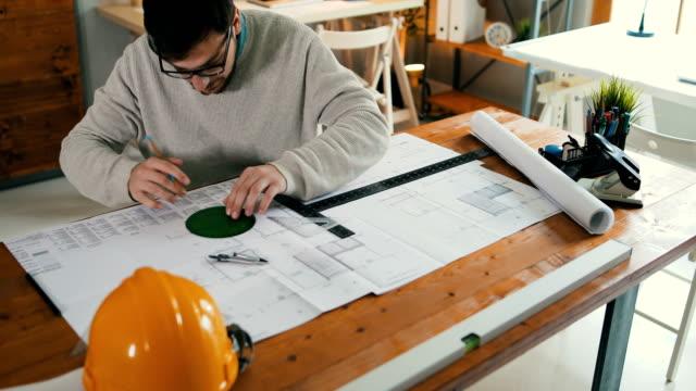 vídeos de stock, filmes e b-roll de jovem arquiteto masculino trabalhando no projeto - plano de arquitetura