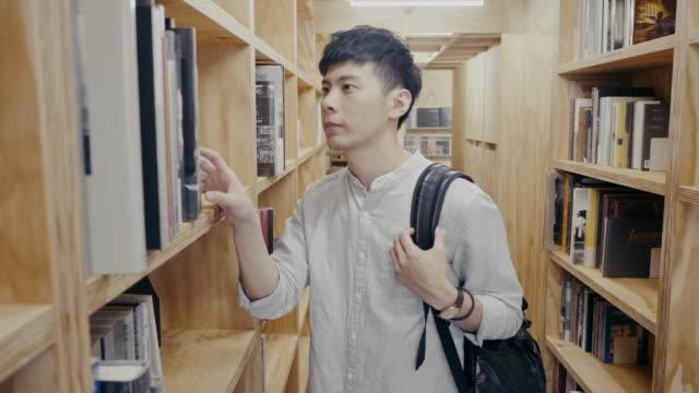 vídeos y material grabado en eventos de stock de joven estudiante universitario asiático masculino busca un libro en la biblioteca (movimiento lento) - un solo hombre