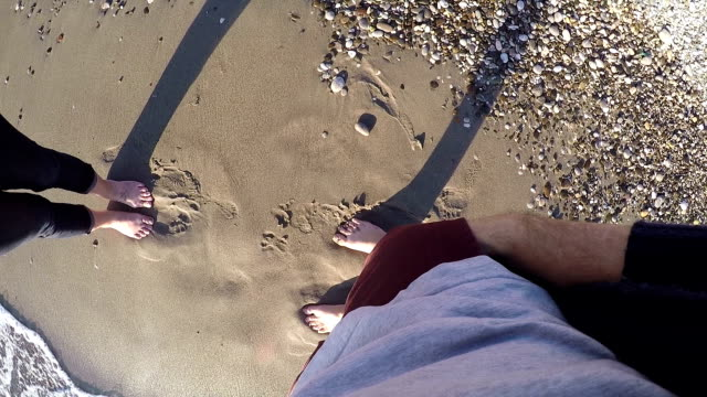 Young male at 30s proposing to his girlfriend at the beach. POV