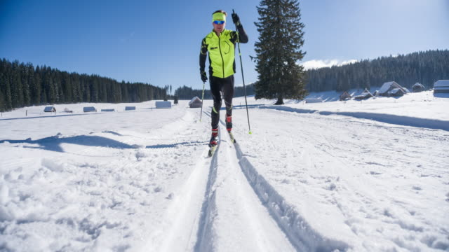 young male athlete cross country skiing on ski track - striding stock videos & royalty-free footage