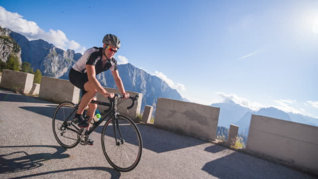 young male athlete cycling on a mountain pass - racing bicycle stock videos and b-roll footage