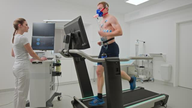 junger männlicher sportler bei einem kardiopulmonaden stresstest auf einem laufband in der klinik - halbbekleidet stock-videos und b-roll-filmmaterial