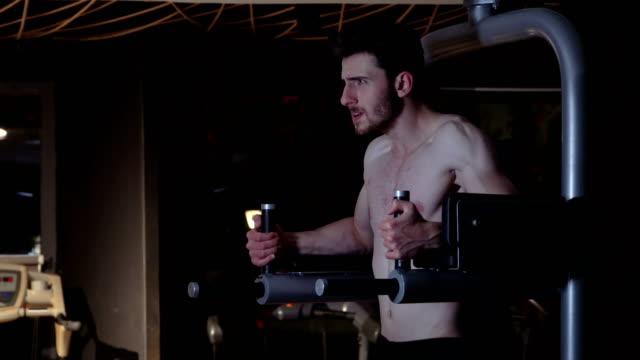 junge männliche athlet tun bein hebt übung im fitnessstudio - menschliches knie stock-videos und b-roll-filmmaterial