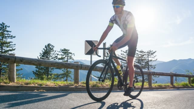 giovane atleta maschio in bicicletta su strada su un passo di montagna - triatleta video stock e b–roll