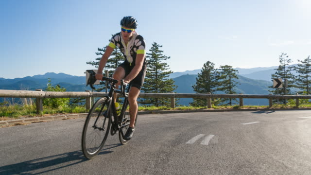 young male athlete road cycling on a mountain pass - racing bicycle stock videos and b-roll footage