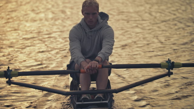 young male athlete rowing boat in river at sunset - sculling stock videos & royalty-free footage