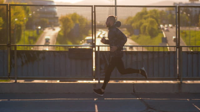 Young male athlete running on a bridge above city traffic