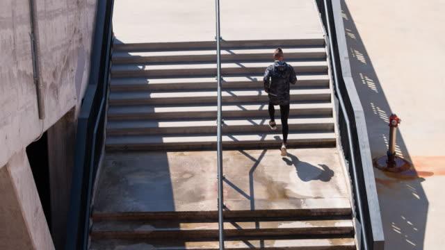 junge männliche athlet läuft die treppen eines stadion - staircase stock-videos und b-roll-filmmaterial