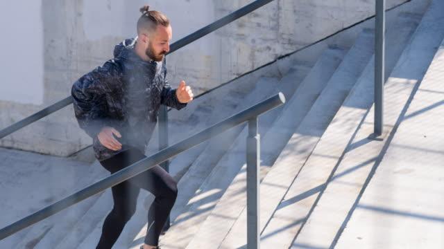 若い男性アスリートのランニングは、階段