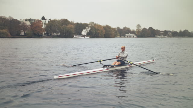 young male athlete sculling rowboat in river - sculling video stock e b–roll