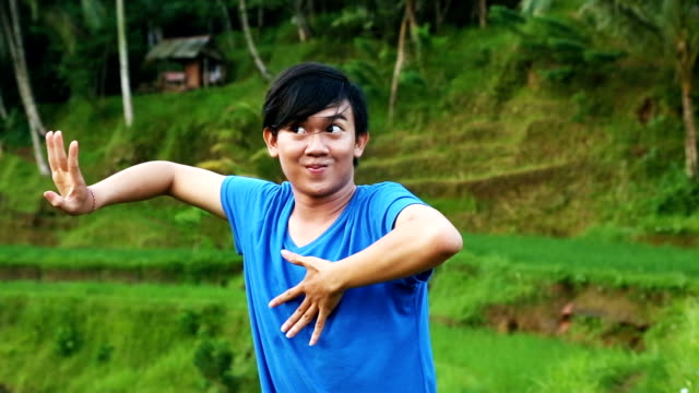 young male balinese dancer practicing choreography outdoors rice paddy - traditional dancing stock videos and b-roll footage