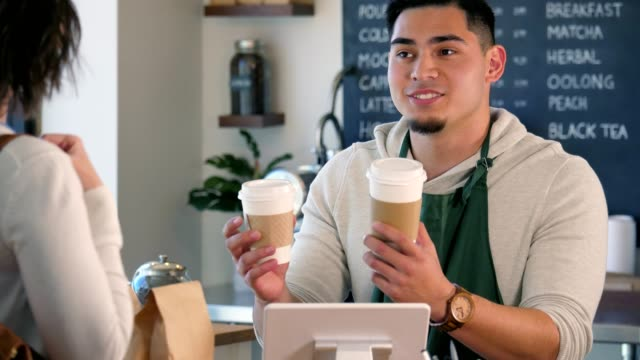 a young, male barista helps a customer decide on her drink size. - take away food stock videos & royalty-free footage