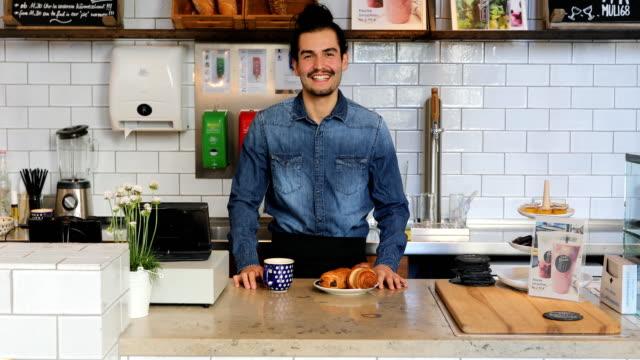 junge männliche barista stehend mit kaffee und essen - arbeitsplatte stock-videos und b-roll-filmmaterial