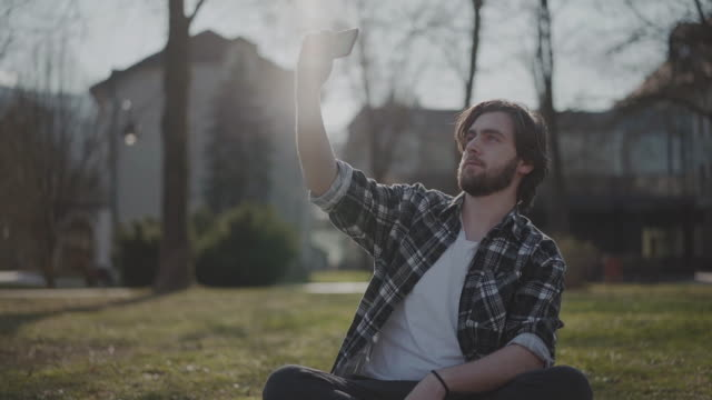 stockvideo's en b-roll-footage met jong mannetje dat bezig op de telefoon door zich in het park buiten in een zonnige de zomerdag met toevallige uitrusting is - bosnië en herzegovina