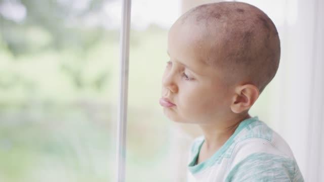 vídeos de stock, filmes e b-roll de jovem masculino câncer paciente olhando pela janela - infância