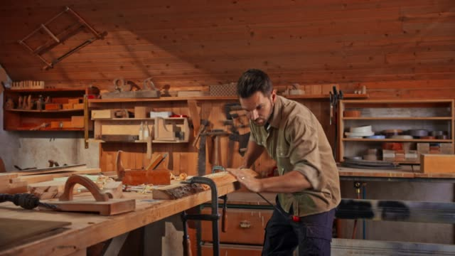 young male carpenter using a drawknife to shape a piece of wood in his shop - accuracy stock videos & royalty-free footage