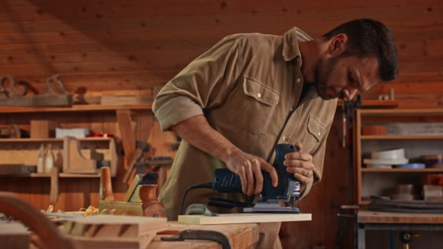 young male carpenter using a jigsaw to cut a piece of wood in his shop - work tool stock videos & royalty-free footage