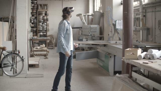 vídeos de stock e filmes b-roll de young male carpenter using vr glasses - small office