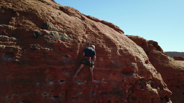 vídeos y material grabado en eventos de stock de joven hombre escalar el acantilado de piedra arenisca - barefoot